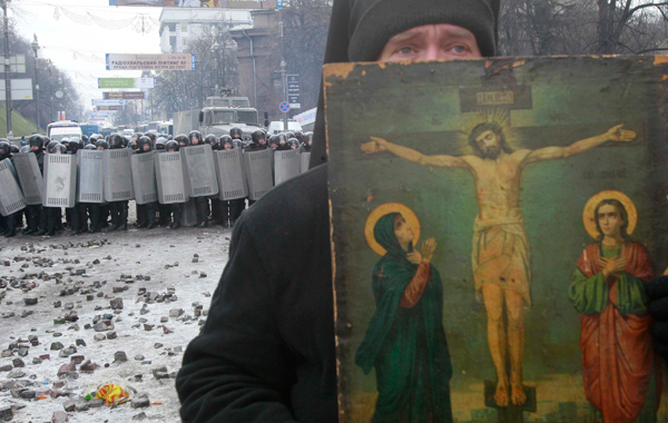 A clergyman holds a religious picture during a rally held by pro-European integration protesters in Kiev