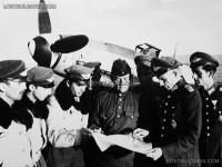 """Български летци и съветски офицери обсъждат летателни задачи. Втори от дясно на ляво полк. Георги Дреников, изпълняващ длъжността Командир на Въздушни войски от 9 септември до 23 октомври 1944 г. Зад тях изтребител Месершмит 109Г - """"Густав""""(Messerschmitt Me-109G), II-ра фаза на Втората световна война, 1944 г."""