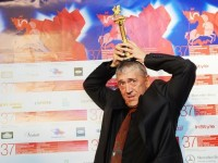 "Ивайло Христов се чуди как да позира с Гран при статуетката ""Златен Георги"" на кинофестивала в Москва."