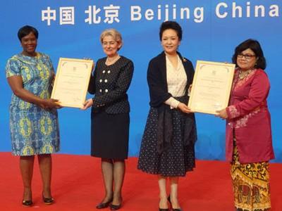 Генералният директор Ирина Бокова и проф. Лиюан Пин, първа дама на Китай и специален посланик на ЮНЕСКО за образованието на момичетата и жените, връчиха първата награда на ЮНЕСКО за образование на момичета и жени на лауреатите от Индонезия и Зимбабве по време на церемония в Пекин на 6 юни 2016 г.
