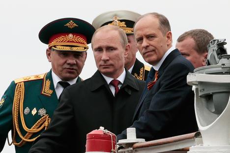 Владимир Путин, министърът на отбраната Сергей Шойгу (отляво) и директорът на ФСБ Александър Бортников. 9 май 2014 г. Снимка: AP