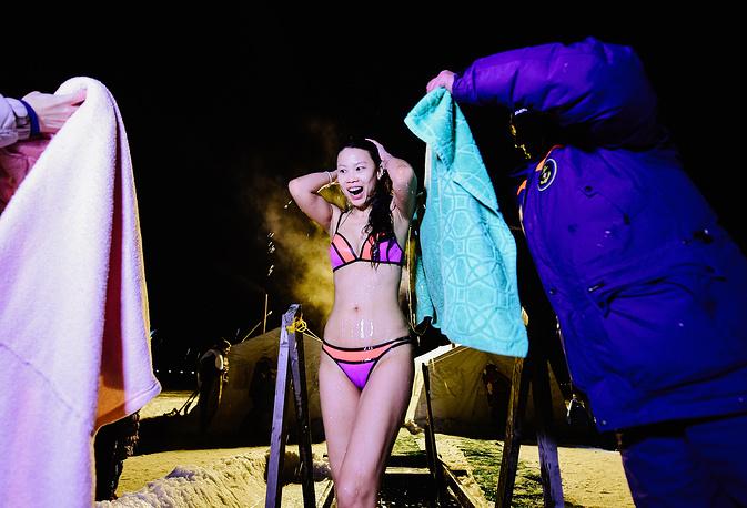 """VLADIVOSTOK, RUSSIA - JANUARY 18, 2017: A girl offered towels after dipping in the icy water during the celebration of Epiphany. In Eastern Christianity, the feast of Epiphany commemorates the Baptism of Jesus. The Russian Orthodox Church celebrates the holiday according to the Julian calendar. Yuri Smityuk/TASS Ðîññèÿ. Âëàäèâîñòîê. 18 ÿíâàðÿ 2017. Äåâóøêà âî âðåìÿ êðåùåíñêèõ êóïàíèé â ïðîðóáè íà áåðåãó Àìóðñêîãî çàëèâà â ðàéîíå æåëåçíîäîðîæíîé ñòàíöèè """"Ñàíàòîðíàÿ"""". Þðèé Ñìèòþê/ÒÀÑÑ"""