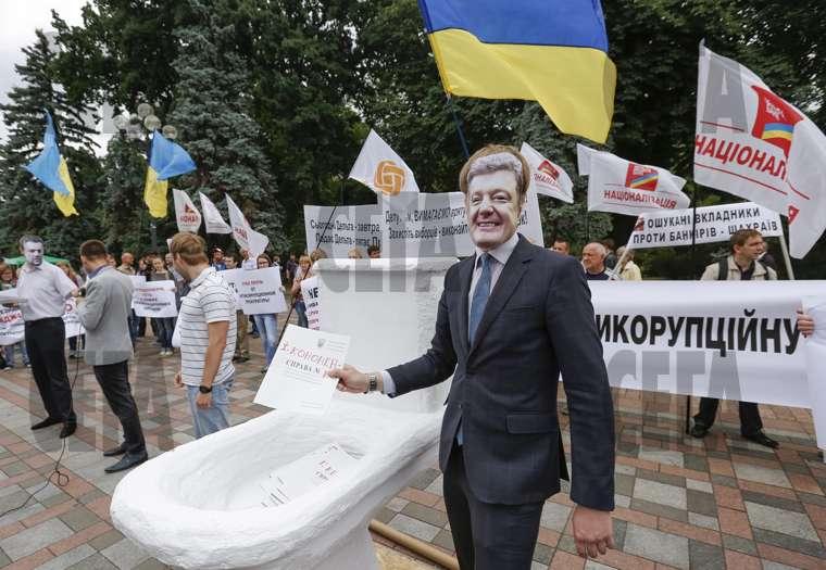 Протестиращ с маска на украинския президент Петро Порошенко слага фиктивни криминални досиета в импровизирана тоалетна чиния по време на демонстрация срещу корупцията в правителството пред украинския парламент в Киев.