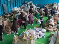 Доброволци сортират хуманитарна помощ да житерите на град Авдеевка, който е под контрола на украинската страна.