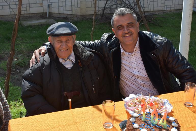 Дядо Георги Георгиев с кмета Димитър Иванов и тортата, на която свещичките изписват 104 години