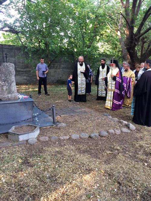 """Митрополит Гавриил прочете заупокойна молитва на гроба в двора на храма """"Света Троица"""". На това място са погребани повече от 200 избити ловчалии, в това число жени и деца."""