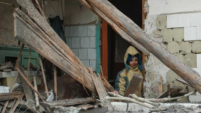 Дете стои пред дома си в Донецк, пострадал от обстрел на украинските части. / БГНЕС